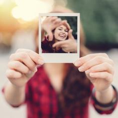 Jeune fille montrant un selfie polaroïd